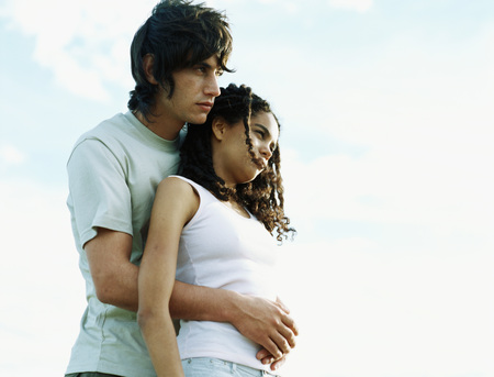 Couple embracing outdoors, looking away, low angle view LANG_EVOIMAGES