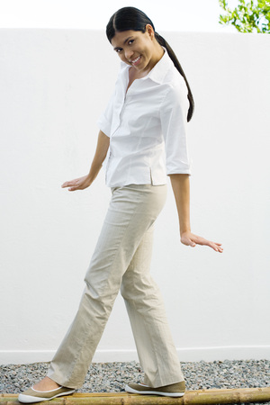Woman standing on bamboo poles, smiling at camera, full length