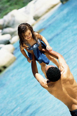 Father lifting daughter in the air at the beach, rear view