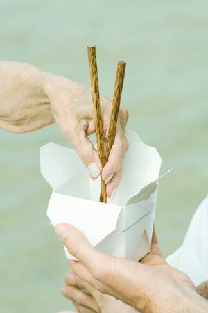 Male hand holding container, senior womans hand reaching in with chopsticks, cropped