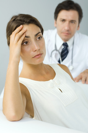 unease: Woman holding head, looking away, doctor in background LANG_EVOIMAGES