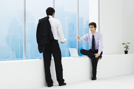 Two businessmen facing each other, one sitting on ledge, one standing