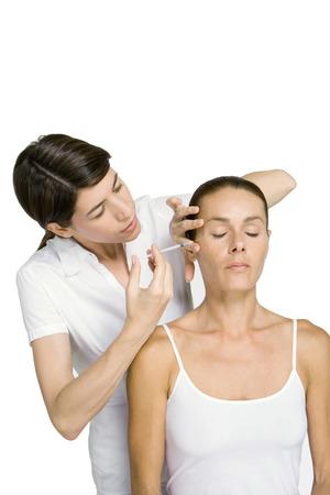 Woman having Botox injection, eyes closed