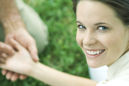 Teen girl holding mans hand, smiling over shoulder at camera, cropped view