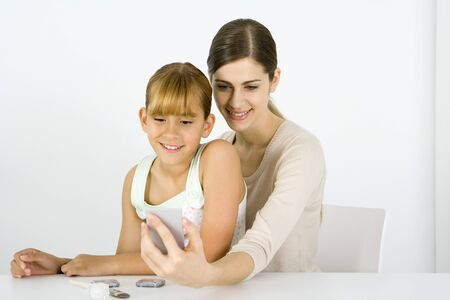 Girl sitting on young womans lap, looking into hand mirror together