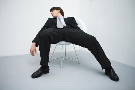 Junger Geschäftsmann, der im Stuhl, die geschlossenen Augen slouching ist