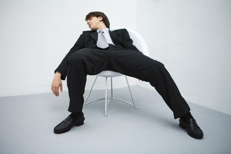 Young businessman slouching in chair, eyes closed