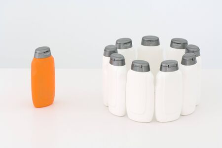 Group of white bottles in circle and single orange bottle