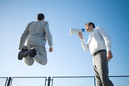 Businessman standing beside colleague, shouting into megaphone, colleague jumping in air, low angle view LANG_EVOIMAGES