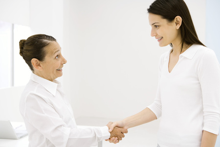Senior woman and young woman shaking hands, side view