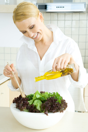 Woman in kitchen, pouring olive oil on large salad