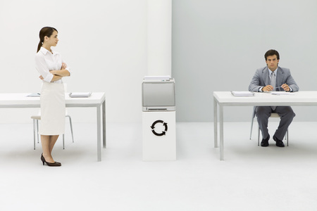 Two professionals in office, woman with arms folded, man looking at camera, circular arrow symbol between them