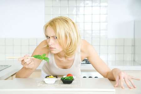 Woman leaning over food, looking at camera threateningly LANG_EVOIMAGES