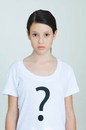 puzzlement: Girl wearing tee-shirt printed with question mark, looking at camera LANG_EVOIMAGES