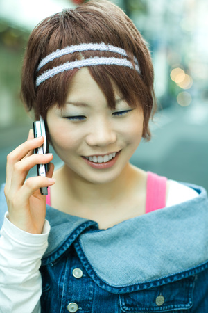 Young Japanese woman using cell phone, smiling LANG_EVOIMAGES