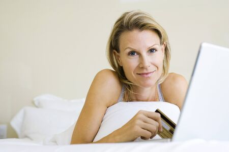 Woman lying on bed, using credit card and laptop, smiling at camera LANG_EVOIMAGES