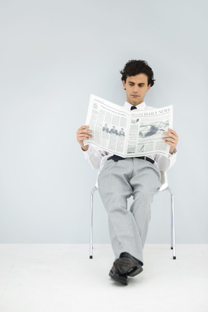 Businessman slouching in chair, reading newspaper LANG_EVOIMAGES