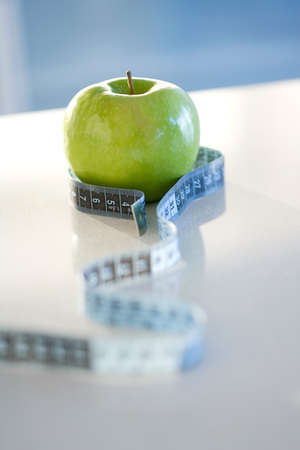 Measuring tape wrapped around green apple, close-up LANG_EVOIMAGES