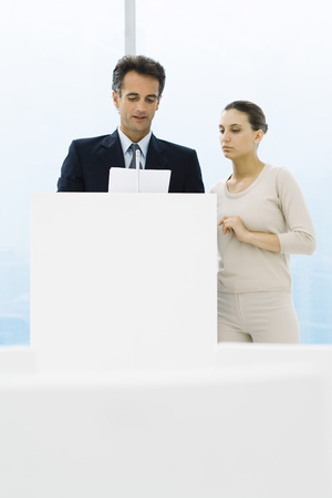 Businessman standing at lectern, discussing document with female assistant