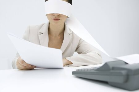 Woman sitting at desk, tape from an adding machine wrapped around her head, holding document
