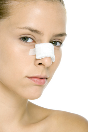 oneself: Woman with bandaged nose, looking at camera, close-up LANG_EVOIMAGES