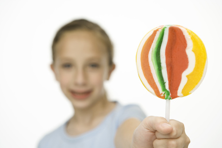 Girl holding up and showing the camera a multicolored lollipop, focus on foreground