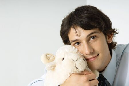 aries: Young man holding stuffed toy against cheek, smiling at camera