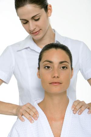 Woman receiving shoulder massage, looking at camera