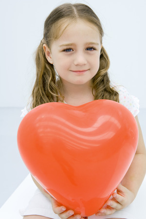 heartshaped: Girl holding large balloon heart, smiling at camera, portrait