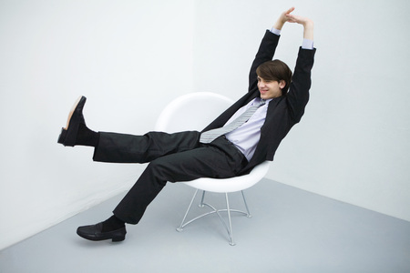 Young man in suit sitting in chair, legs outstretched, arms raised, full length LANG_EVOIMAGES