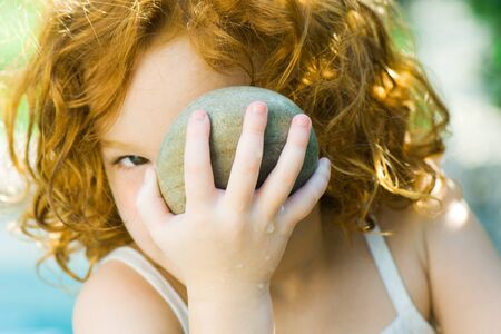 Girl holding up stone to face