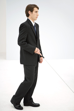 Businessman walking with white cane, side view LANG_EVOIMAGES