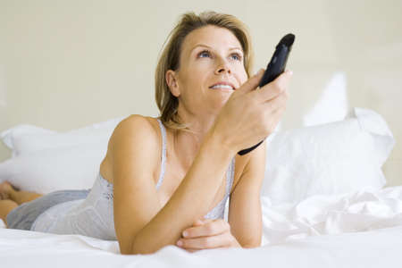 Woman lying on bed, changing channel with remote control LANG_EVOIMAGES