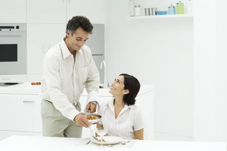 Couple together at kitchen table, man serving womans dinner, both smiling LANG_EVOIMAGES