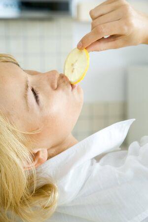 Woman eating lemon slice, head back, cropped view