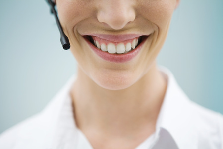 Young woman in headset, smiling at camera, cropped view LANG_EVOIMAGES