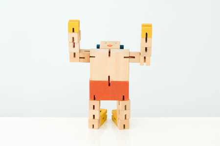 Wooden robot kneeling with head back and arms raised