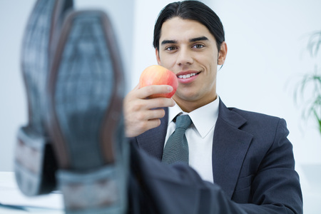Young professional man sitting with feet up, holding apple and smiling at camera