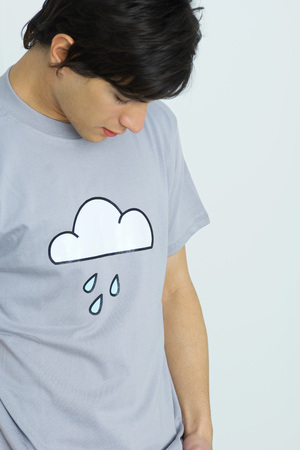 Young man wearing tee-shirt printed with cloud and raindrops, head down