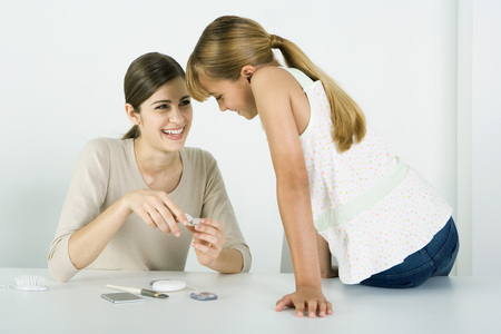 teaches: Young woman and preteen sister looking at cosmetics together, smiling