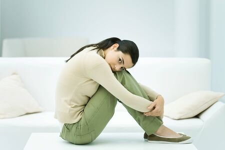 Woman sitting on coffee table, hugging knees, looking at camera LANG_EVOIMAGES