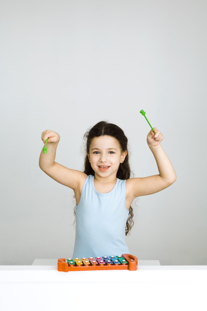 Little girl playing xylophone, arms raised, looking at camera LANG_EVOIMAGES