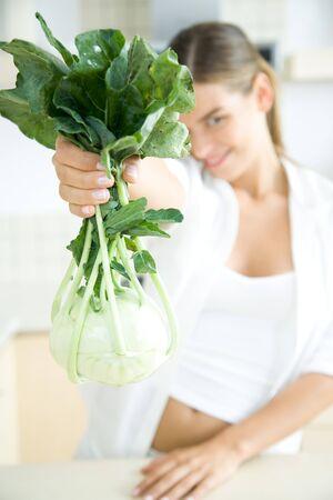 Woman holding up fresh kohlrabi, smiling at camera