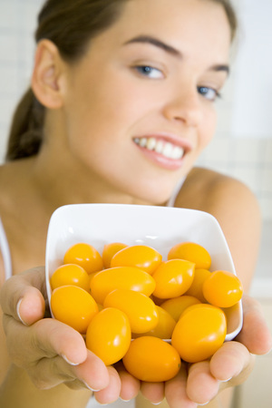 Young woman holding out bowl of yellow cherry tomatoes LANG_EVOIMAGES