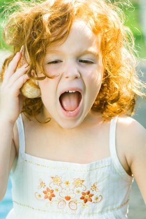 Girl listening to seashell, shouting
