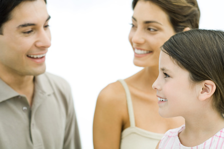 Parents and young daughter smiling at each other, close-up