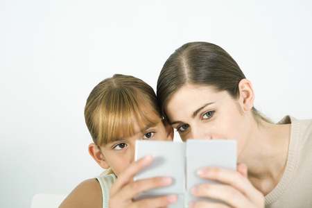 Woman and girl cheek to cheek, looking into hand mirrors