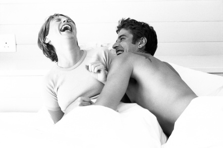 Couple in bed, both laughing
