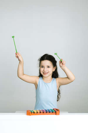 xilofono: Little girl playing xylophone, arms raised, smiling