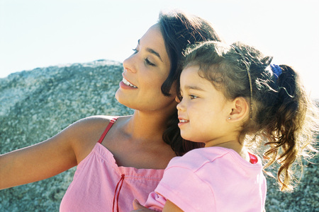 Mother and daughter looking away outdoors, smiling, side view LANG_EVOIMAGES